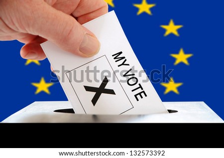 Voting slip being placed by a white hand into a ballot box with the European Union flag in the background
