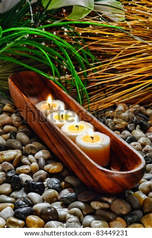 Votive candles burning with a soft glow flame in a traditional carved wood vessel holder on a bed of pebbles among lush vegetation for a soothing relaxation ambiance in a holistic spa - stock photo