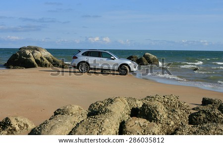 Vung Tau, Vietnam - April 20, 2012: A luxury sport car running on sand terrain of the beach side under the sunlight in a off-road test drive.  - stock photo