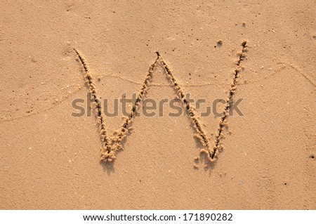 W text written in the sandy on the beach - stock photo
