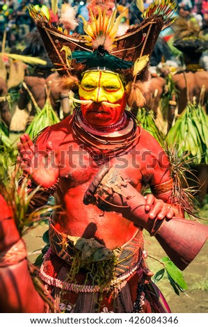 Wabag, Papua New Guinea - circa August 2015: Native half-naked man with red and yellow colours on his face during traditional Enga cultural show in Wabag, Papua New Guinea. Documentary editorial.
