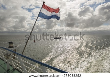 Wadden Sea with Dutch flag as seen from the ferry form the town of Harlingen to Terschelling  - stock photo