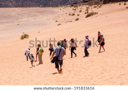 WADI RUM, JORDAN - APR 30, 2014: Unidentified tourists walk over the Wadi Rum valley. Wadi Rum valley is the UNESCO World Heritage site