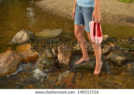 Wading in Creek - Young woman with shoes in hand, cooling off her feet in a creek in the Belgian Ardennes  - stock photo