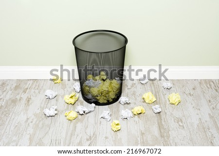 Wads of crumpled up paper scattered in and around a trashcan shows the frustration of an office worker. Image can be easily cropped and used as a vertical depending on buyer needs. - stock photo