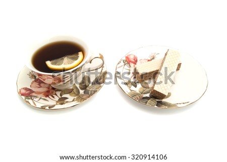 wafer and cup of tea with lemon closeup on white