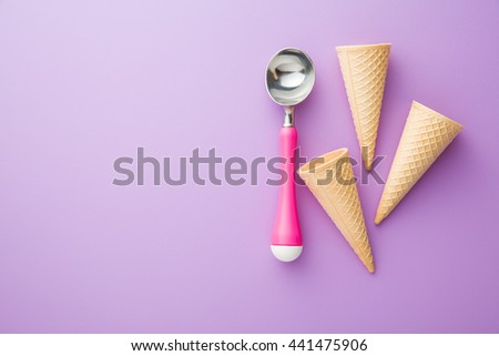 wafer cone and ice cream scoop on violet background. Top view. - stock photo
