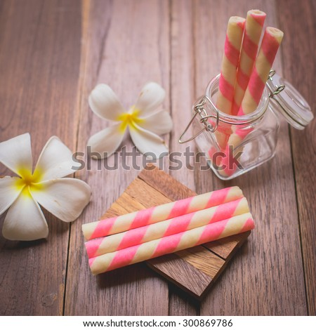Wafer roll sticks glass bottle and wooden table