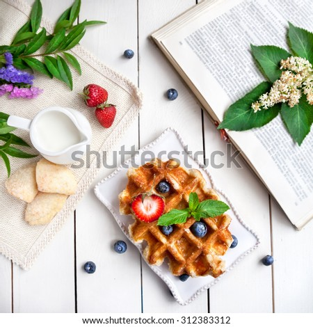 Wafers with berries, book and flowers on the white table  - stock photo