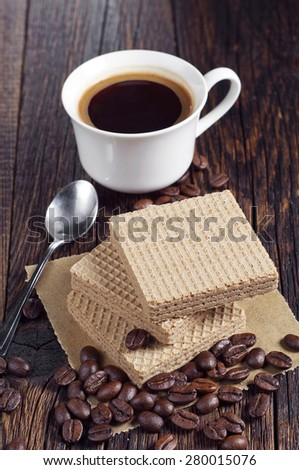 Wafers with caramelized condensed milk and cup of hot coffee on rustic wooden table - stock photo
