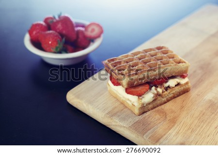 Waffle sandwich with caramel ice cream dessert on wood cutting board with strawberries  - stock photo