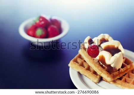 Waffle with caramel ice cream dessert on white plate with strawberries  - stock photo