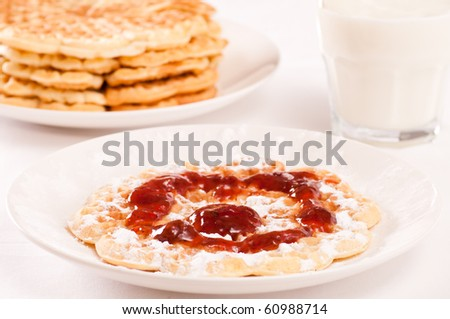 Waffle with strawberry jam, powdered sugar and milk. Waffles in background - stock photo