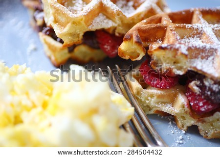 Waffles filled with fresh raspberries and chocolate spread and scrambled eggs alongside - stock photo