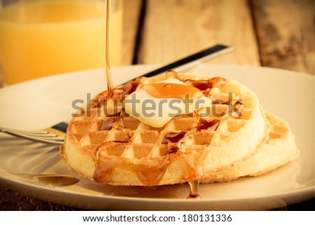 Waffles - This s a photo of a couple waffles being soaked in syrup. Shot in a warm retro color tone with a shallow depth of field. - stock photo