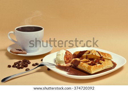 Waffles with a scoop of ice cream with chocolate sauce and a Cup of coffee - stock photo