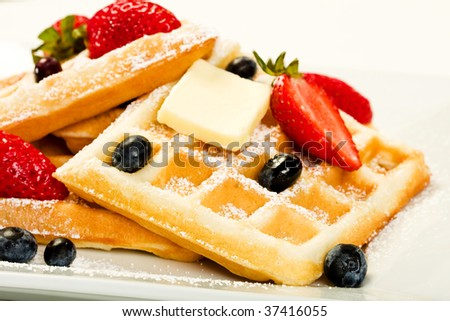 Waffles with strawberries and blueberries on white
