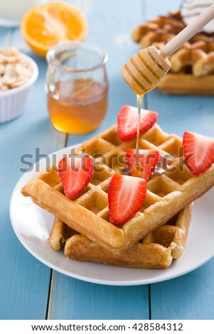 Waffles with strawberries on blue background