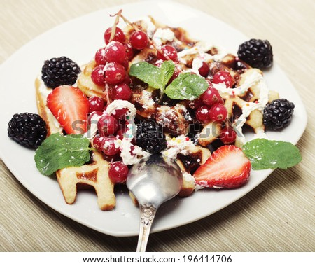 waffles with strawberry and blackberry, over white plate