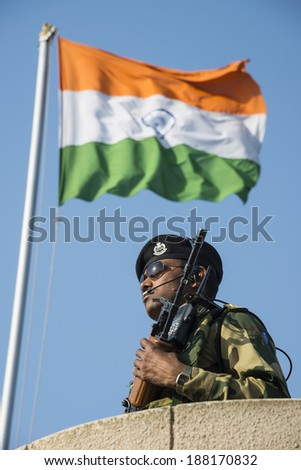 WAGAH, INDIA - APR 11:An Indian soldier keeping watch at the India-Pakistan border, Wagah near Amritsar with Indian Tricolor fluttering in the background on April 11, 2014 in Wagah, India
