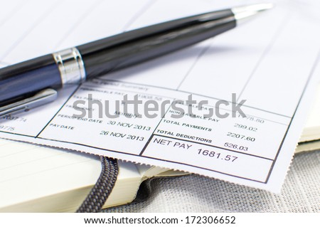 Wage Slip on notepad with black pen in background  - stock photo