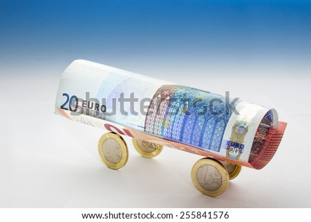 Wagon of 20 and 10 euro banknotes and four euro coins  in blue gradient a background - stock photo