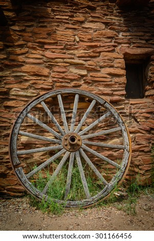 WAGON WHEEL-JUL 2105; lone wheel against building South Rim Grand Canyon