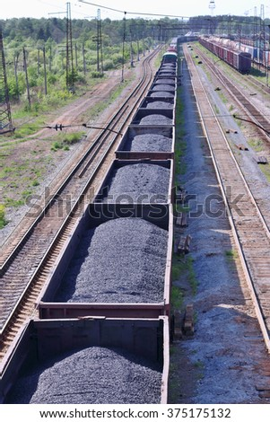 Wagons with coal and railroad tracks near forest in summer sunny day - stock photo