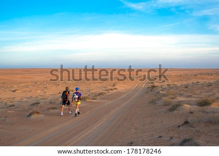 WAHIBA DESERT, OMAN - JANUARY 29: Winners of extreme endurance marathon Transomania 2014, Joao Oliveira and Johan Steene, evening before arriving to the finish point, on January 29, 2014. - stock photo