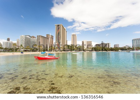 Waikiki beach and red sail boat - stock photo