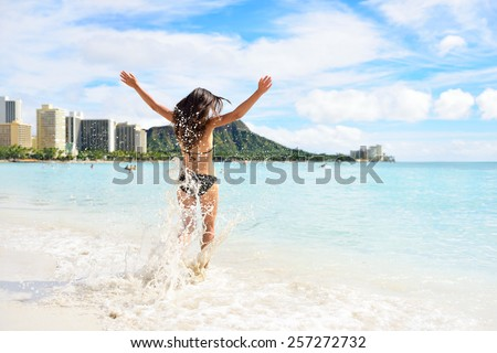 Waikiki beach fun - happy woman on Hawaii vacation. Unrecognizable young adult from behind jumping of joy in water waves, arms up with diamond head mountain in the background, landmark of Honolulu. - stock photo
