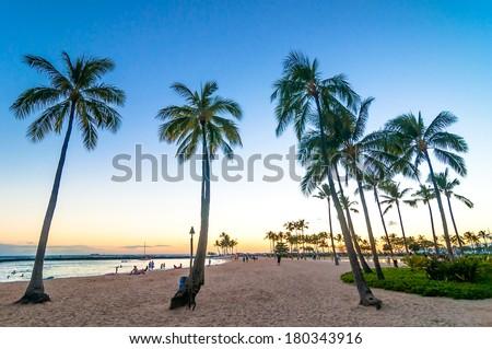 WAIKIKI, HAWAII - SEPTEMBER 7, 2013: sunset time in Waikiki beach, Honolulu, Hawaii. Waikiki white sand beach shoreline is Hawaii's most famous beach. - stock photo
