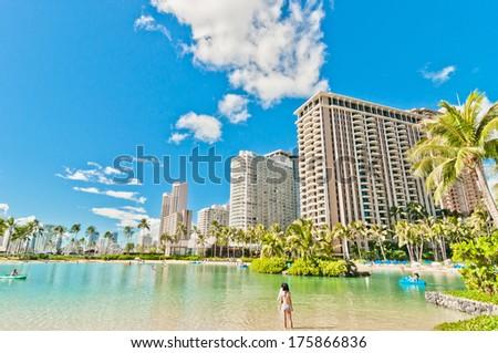 WAIKIKI, HAWAII - SEPTEMBER 7, 2013: Tourists sunbathing and swimming on Waikiki beach in Honolulu, Hawaii. Waikiki white sand beach shoreline is Hawaii's most famous beach. - stock photo