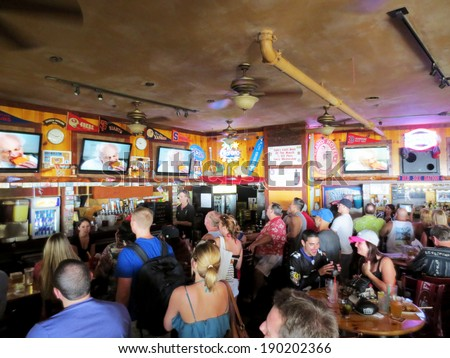 WAIKIKI, OAHU - FEBRUARY 3:  Crowd People watch Taco Bell Superbowl Commercial at iconic Lulu's Bar.  SupeBowl commercials cost roughly $3.8 million a piece taken February 3, 2013 Waikiki, Hawaii. - stock photo