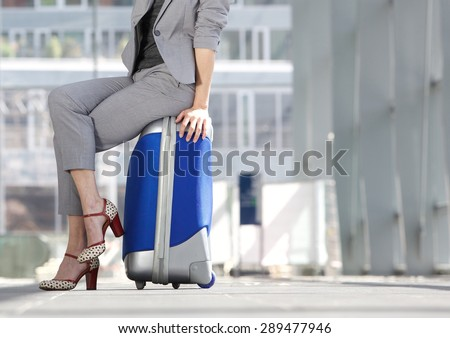 Waist down business woman sitting on suitcase at airport - stock photo