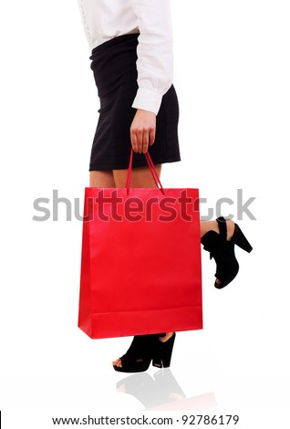 waist-down view of woman carrying a red shopping bag