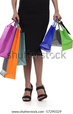 Waist-down view of young woman carrying colorful shopping bags - stock photo