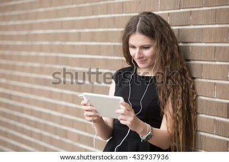 Waist portrait of young woman standing in the street beside brick wall, listening music online with headphones from tablet. Happy beautiful woman using electronic device, looking at screen. Copy space - stock photo