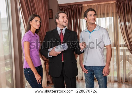 waist up of male real estate agent smiling with two clients. happy agent holding plan of new apartment and looking away - stock photo
