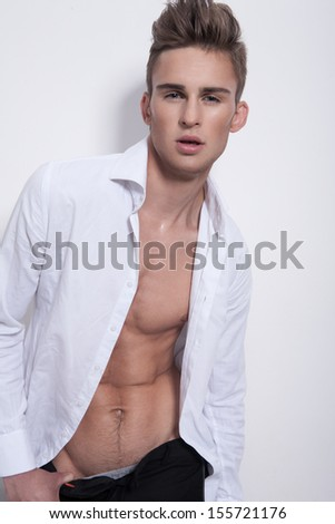 Waist up of sensual young guy with attractive face and fashionable hairstyle, dressed in stylish white unbuttoned shirt - stock photo