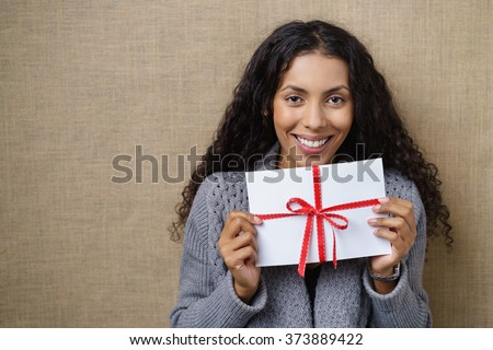 Waist Up of Smiling Young Woman with Curly Dark Hair Looking Excited and Holding White Envelope Wrapped with Red Ribbon and Bow in Studio with Textured Beige Background and Copy Space - stock photo