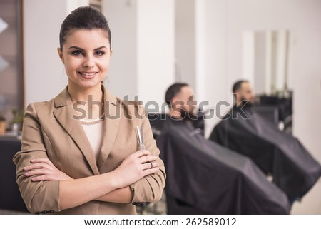 Waist up of young beautiful hairdresser in salon. Client on the background. - stock photo