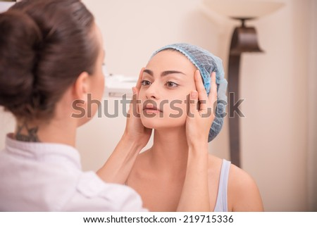 Waist-up portrait of a cosmetologist inspecting skin of her patient a young woman with fresh and clean skin after a professional cosmetology procedures with selective focus on a client - stock photo