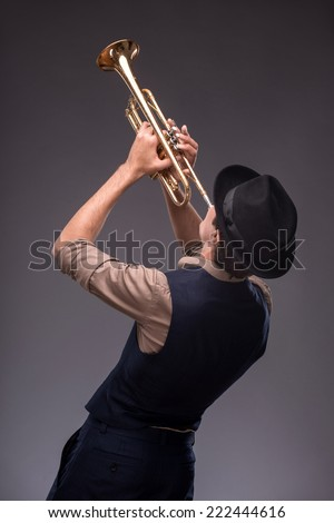 Waist-up portrait of a jazz man in a suit with a black hat hiding his face and standing back to the camera while playing a trumpet isolated on grey background with copy place, concept of jazz music - stock photo