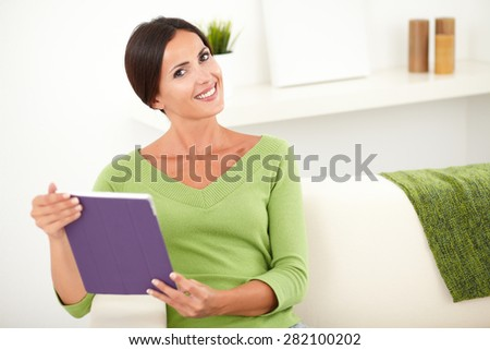 Waist up portrait of a peaceful young female holding a tablet while smiling at the camera - copy space - stock photo