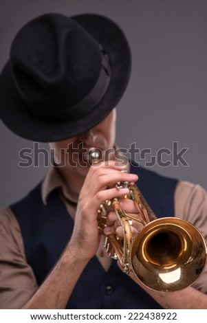 Waist-up portrait of a young handsome Caucasian jazz man in a suit with a black hat looking at the camera with astonishment holding a trumpet in his hand isolated on grey background with copy place