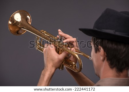 Waist-up portrait of a young handsome Caucasian jazz man in a suit with a black hat looking at the camera holding a trumpet in his hand and playing on it, isolated on grey background with copy place - stock photo