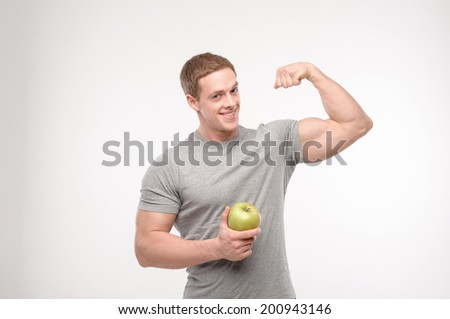 Waist up portrait of an athletic man holding a fresh apple and showing muscles, isolated over a white background. Concept of sport, health - stock photo