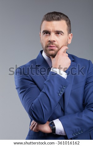 Waist up portrait of attractive businessman is making serious decision. He is standing and touching his beard. The man is looking forward pensively. Isolated on grey background - stock photo