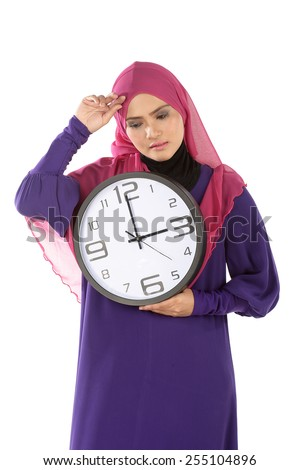 Waist-up portrait of beautiful tired Muslim girl holding with pleasure a big clock in her hands - stock photo